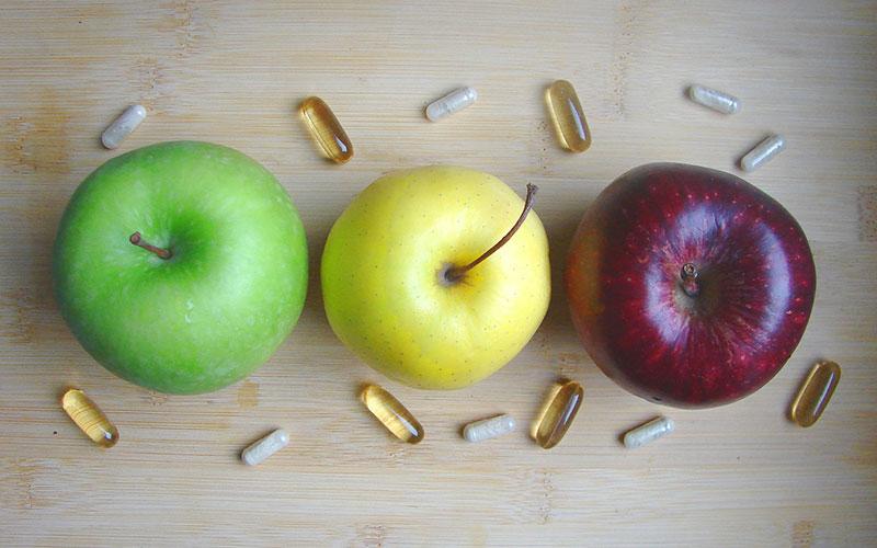 Três maçãs e pilulas de vitaminas